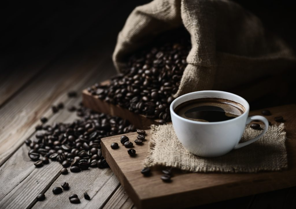 coffee cups and coffee beans on a wooden table